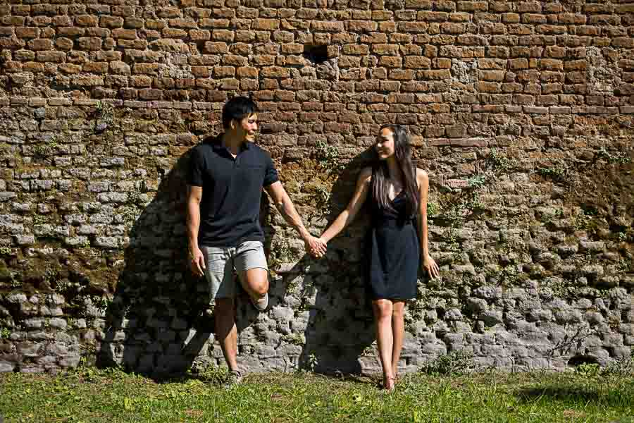 Couple holding hands and posing against an old roman wall