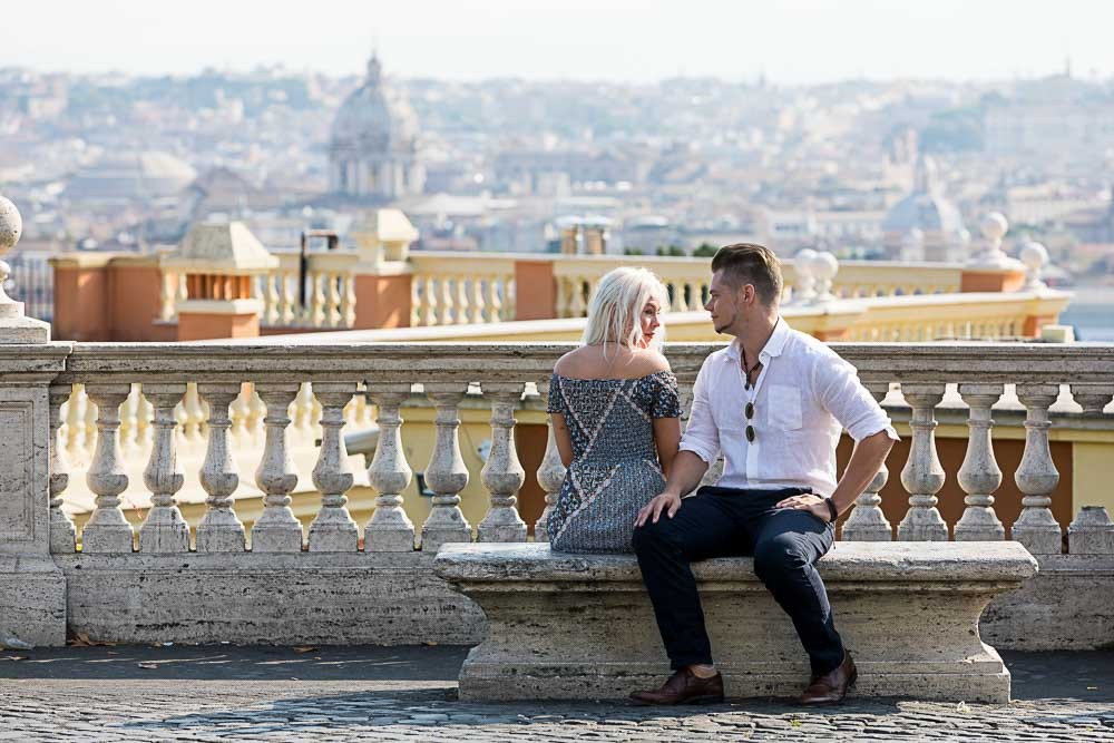 Sitting down couple portrait overlooking the beautiful roman city in the distance