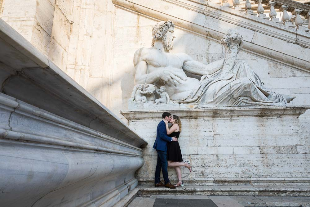 Portrait of a newly engaged couple under a giant marble statue