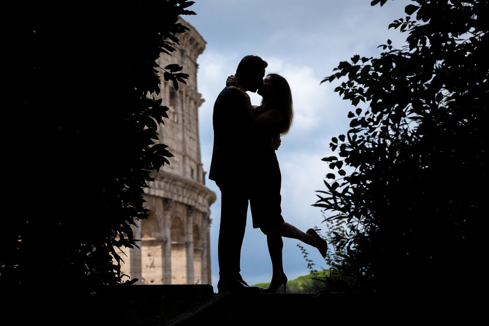 Silhouette image of a couple posing in front of the roman Coliseum in Rome Italy.