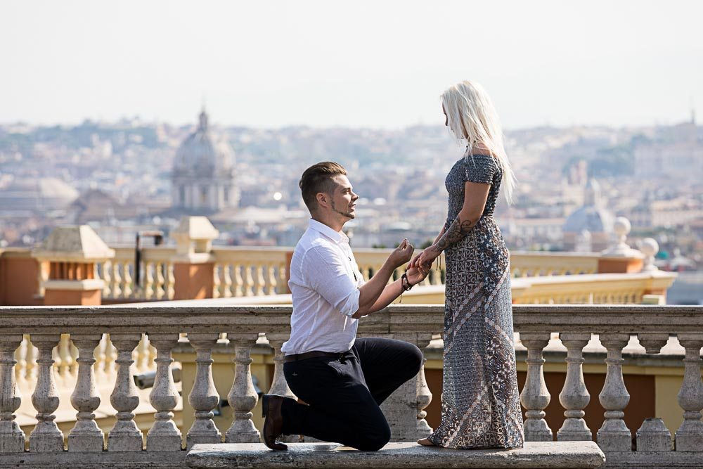 Kneel down Surprising Wedding Proposal at the Janiculum hill in Rome Italy photographed from a distance