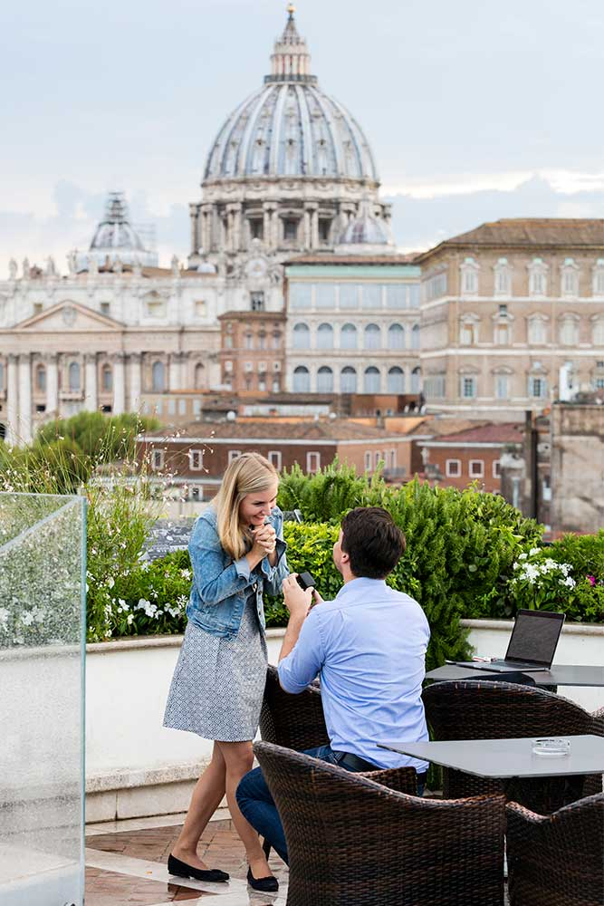 Man proposing on a terrace over a unique view over Rome's Saint Peter's cathedral in the far distance