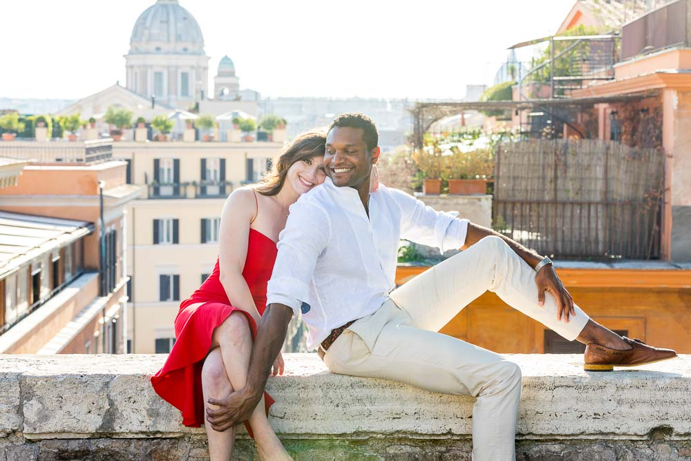 Couple posing sitting down on a ledge with the roman rooftops in the background