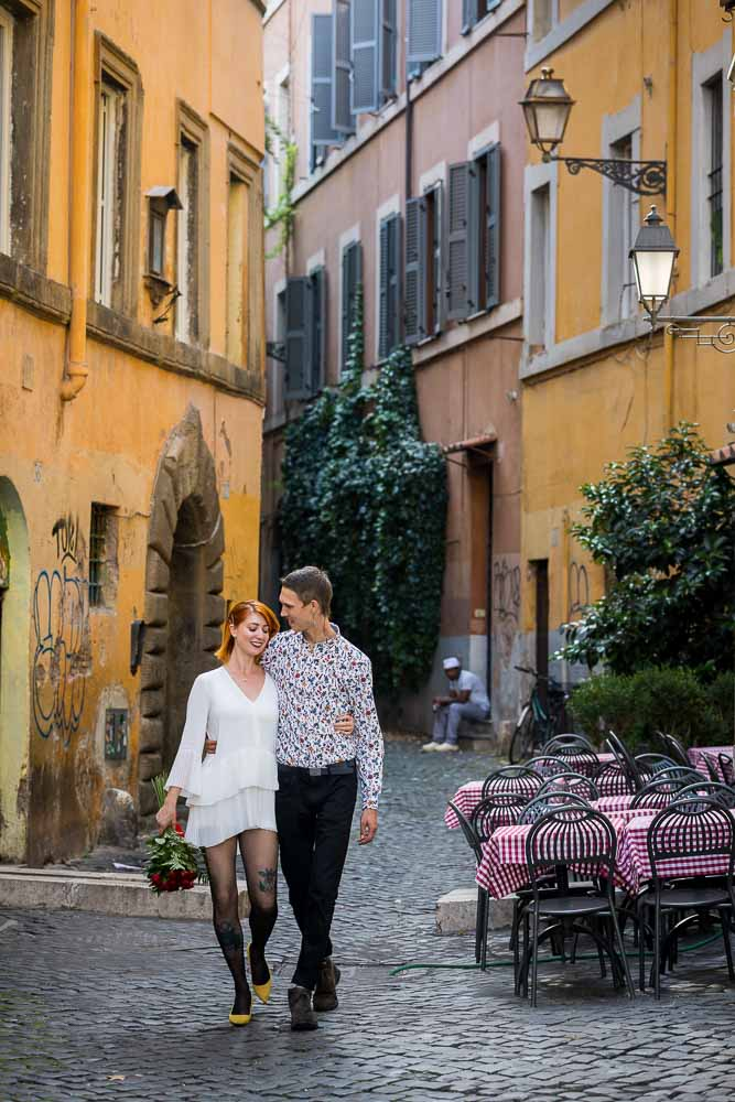 Romantic picture of a couple walking close together in the characteristic streets of Rome Italy