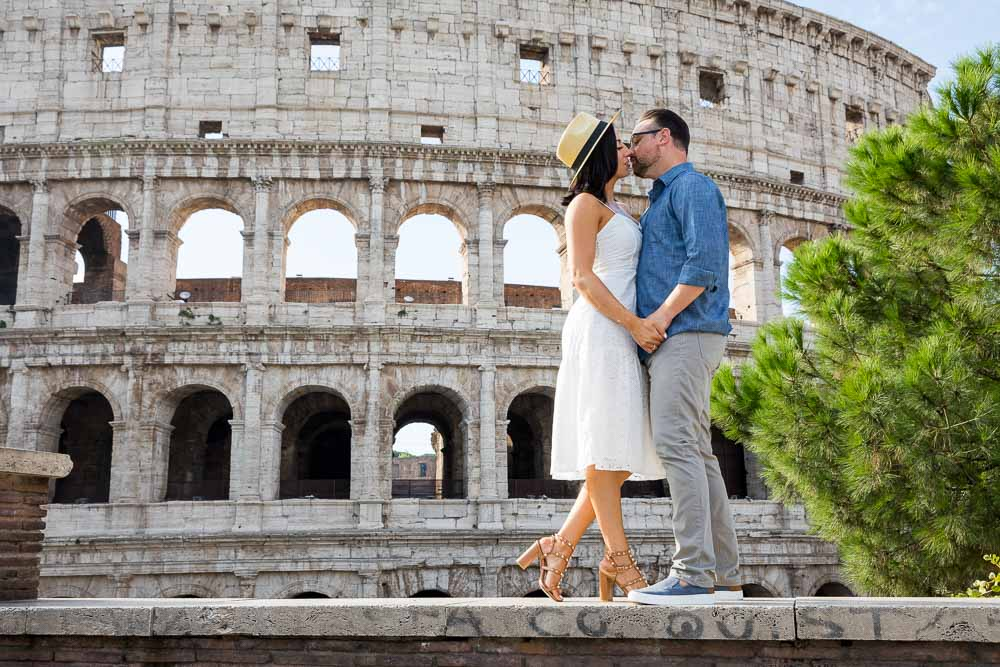 Standing on a ledge kissing before the Roman Colosseum view