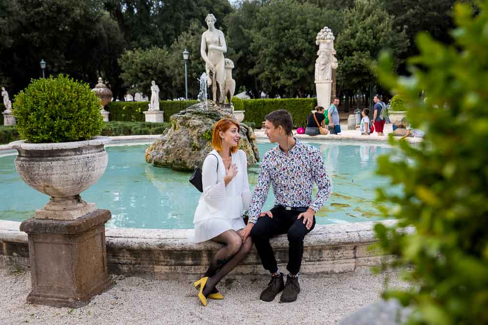 Sitting on the edge of a circular water fountain in a typical Italian style garden