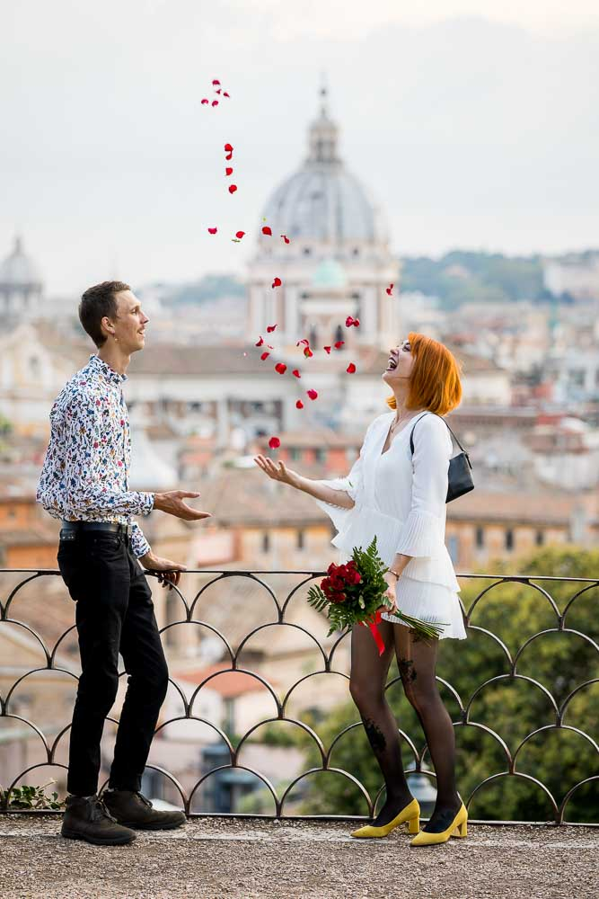 Throwing rose petals in the air from Parco del Pincio overlooking the roman skyline from above
