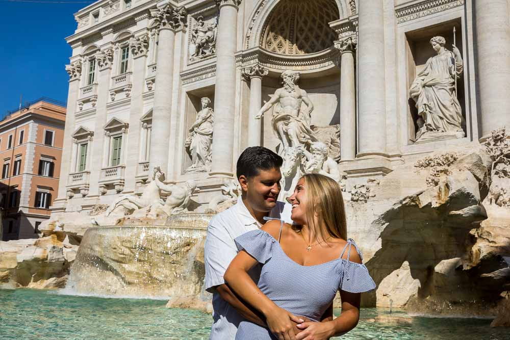 Couple posing while taking photos at the Trevi fountain