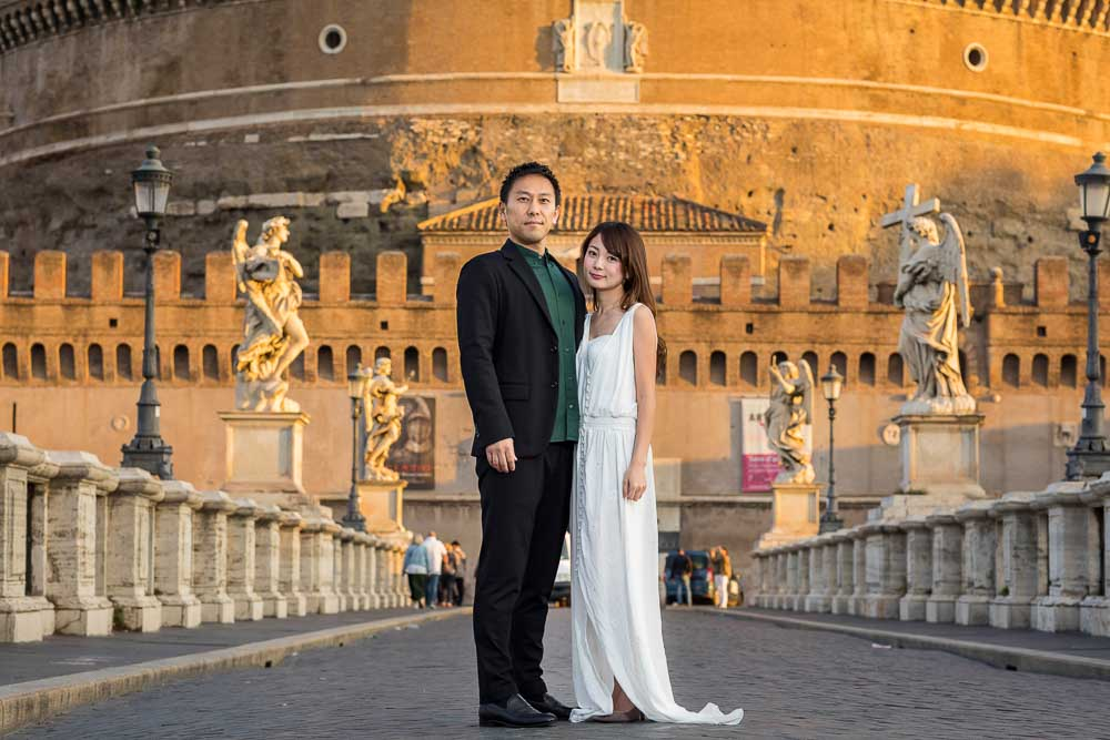 Wedding Couple Photo Session Photography in Rome Italy standing on the ponte Castel Sant'Angelo. Early morning portrait
