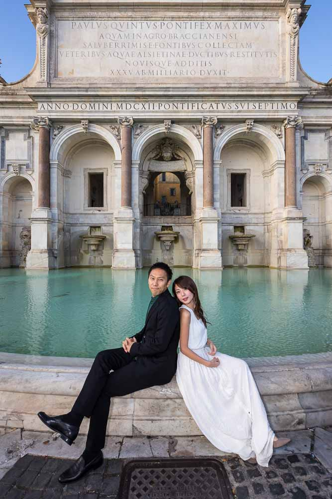 Portrait image of newlyweds sitting on the edge of the Fontanone water fountain