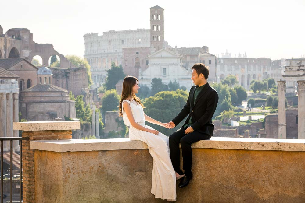 Holding hands before the scenic view of ancient Rome with the Coliseum in the far distance