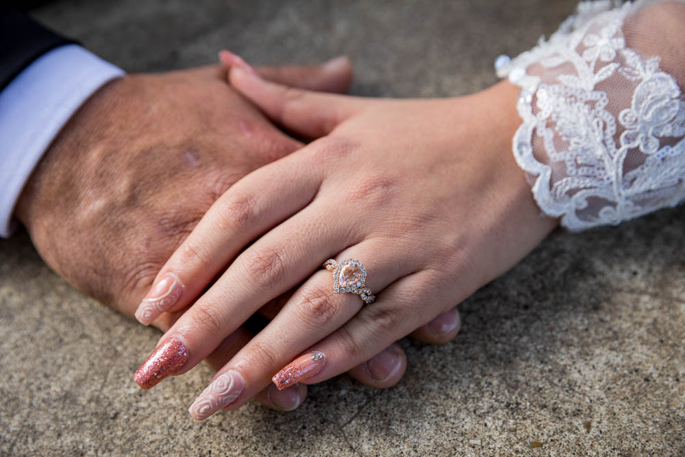 The engagement ring photographed on the hand of the bride over the groom's hand
