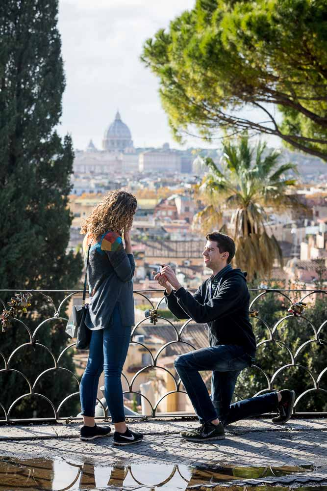 Knee down surprise wedding marriage proposal photographed with Saint Peter's dome in the far distance