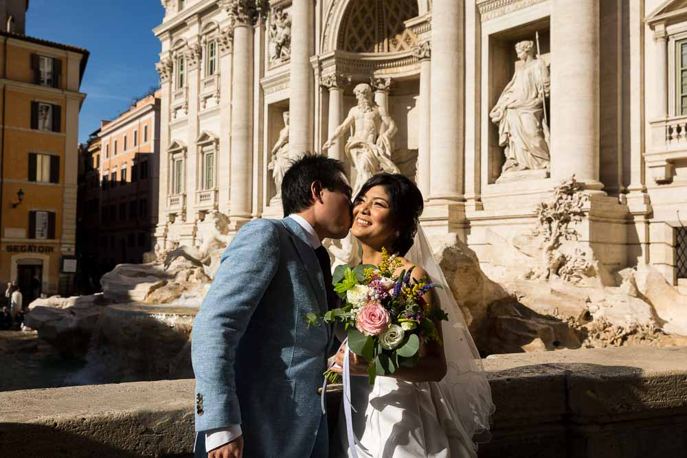 Groom kissing Bride in front of the Trevi fountain in soft midday sunlight
