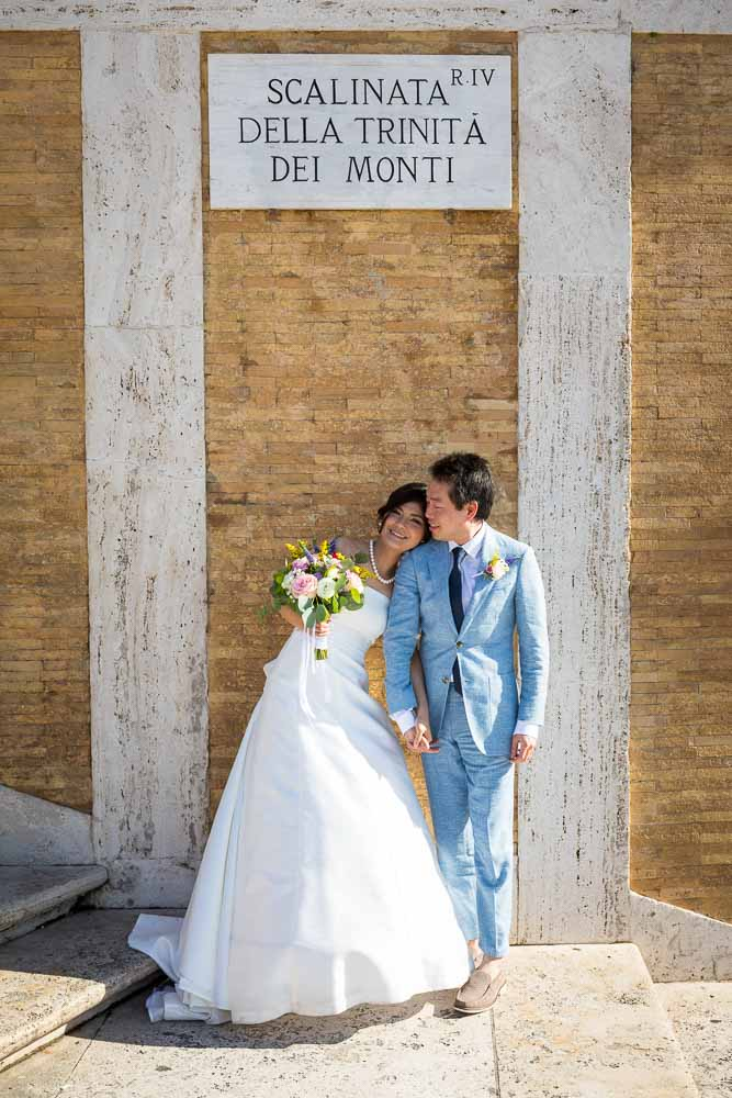Newlyweds standing and posing together while leaning against the wall beneath the Trinita dei Monti sign