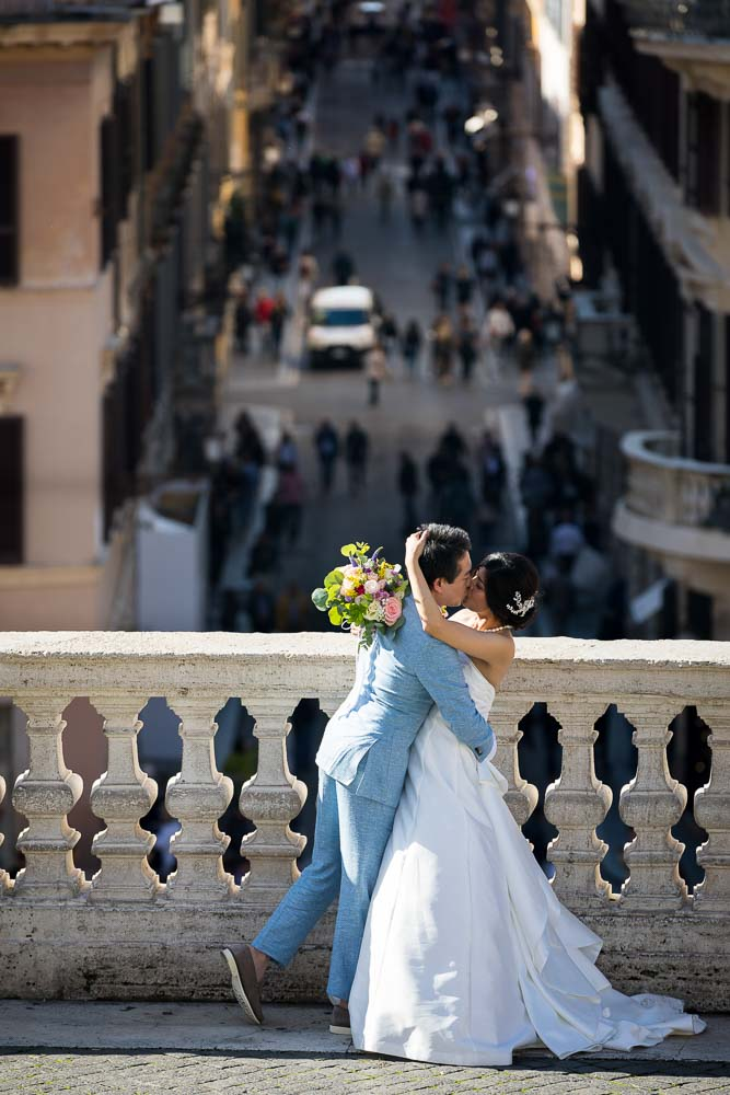 Romantic image of a wed couple close together by the marble balconade