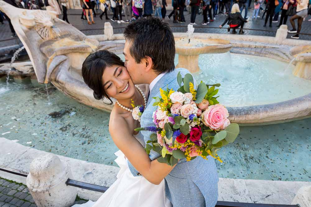 Married and in love taking photography by the Barcaccia water fountain holding the beautiful bouquet in one hand