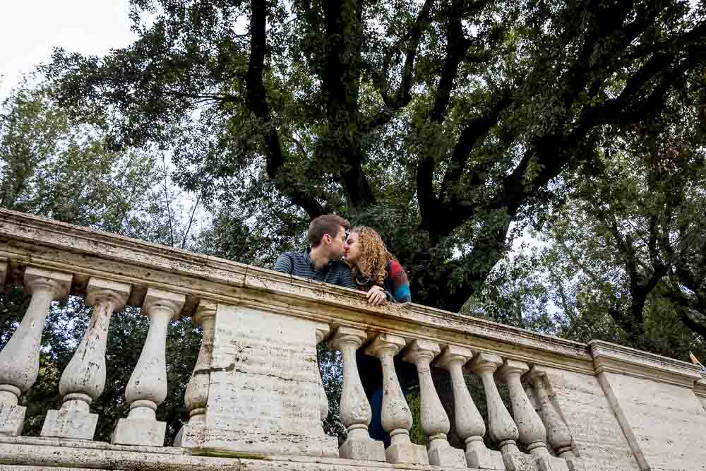 Romantic image of a couple in love underneath a large green tree in Rome' Villa Borghese park