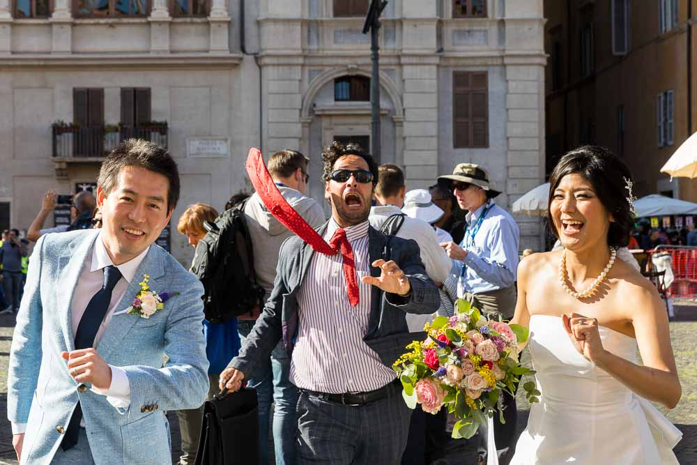 Funny wedding picture of bride and groom chased by a strange businessman