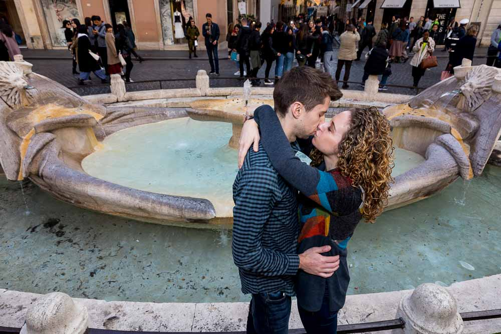 Kissing close together in front of the Barcaccia water fountain