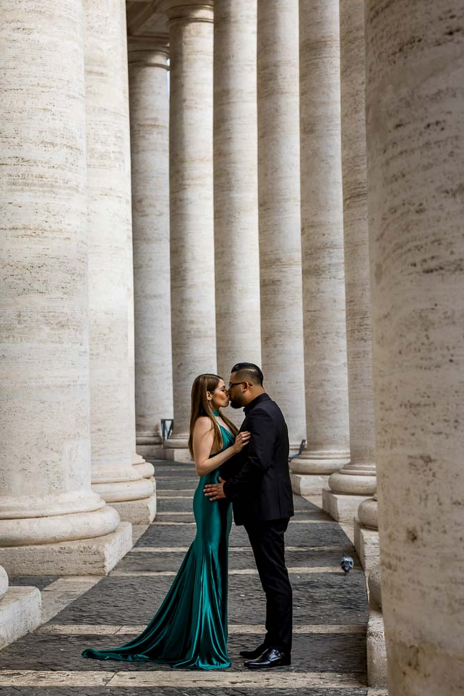 Couple standing kissing underneath the massive marble columns found in Saint Peter's square in the Vatican