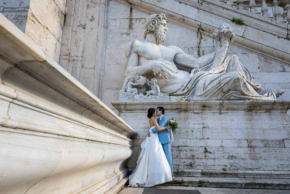 Romantic wedding photography set underneath an ancient roman marble statue found in Piazza del Campidoglio in Rome Italy.