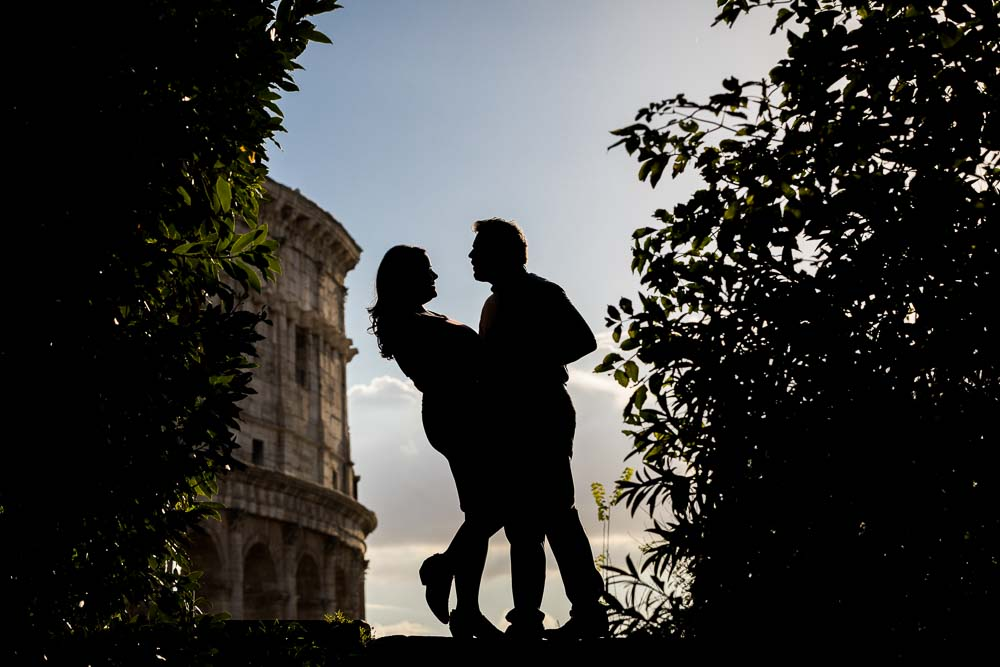 Artistic silhouette image of a couple standing before Rome's colosseum