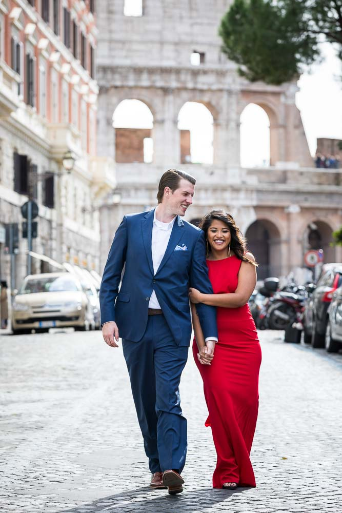Walking hand in hand in the city of Rome with the Colosseum in the background