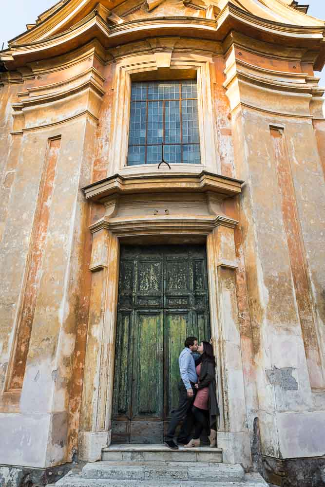 Romantic portrait picture in front of a green door underneath an old building
