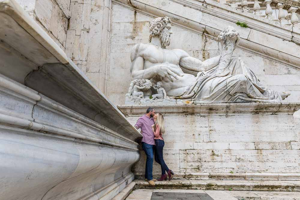 Kissing under a large marble statue in Rome Italy photoshoot