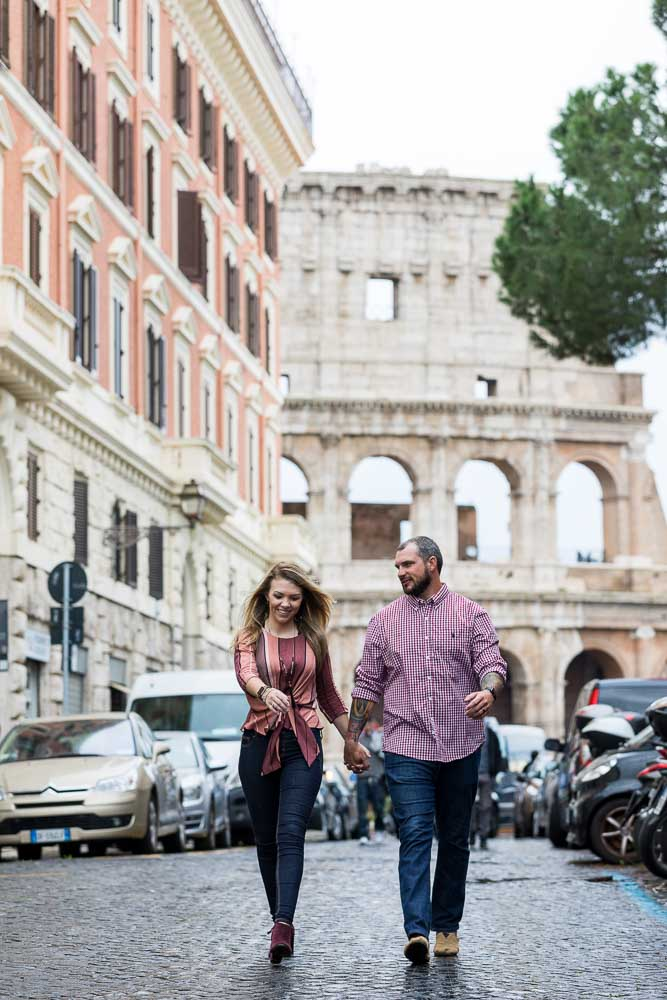 Walking together on a typical roman alleyway street with the Coliseum in the background