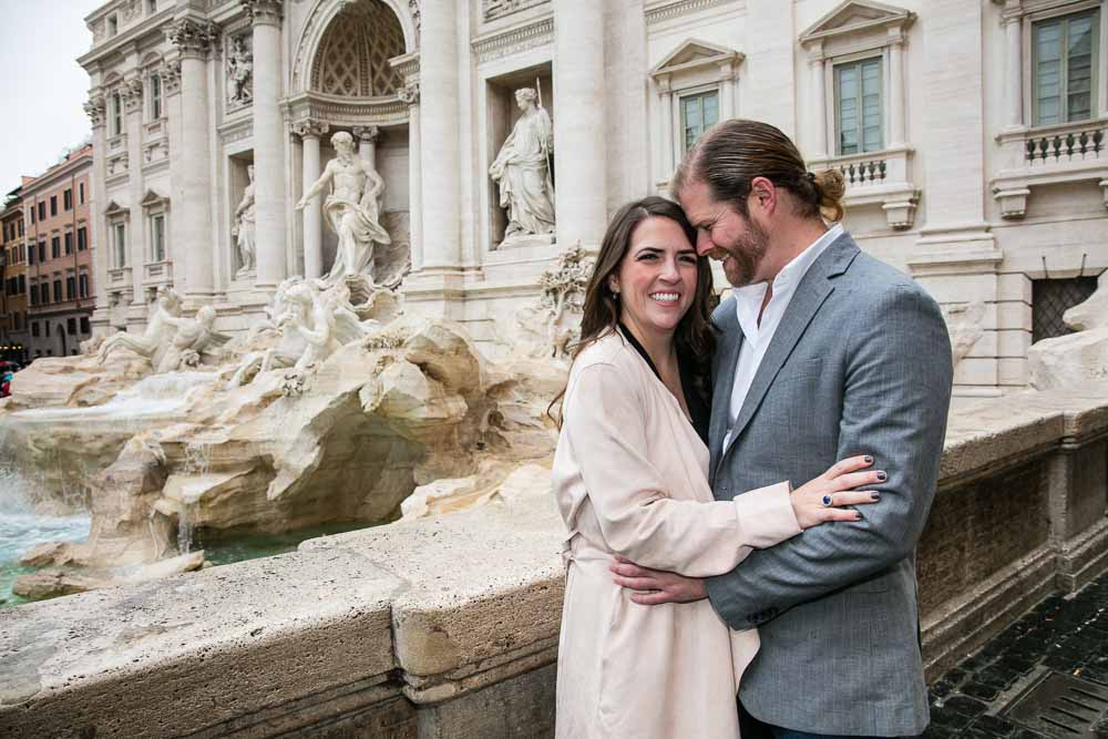 Couple posing in Rome's Trevi fountain during an engagement photo session