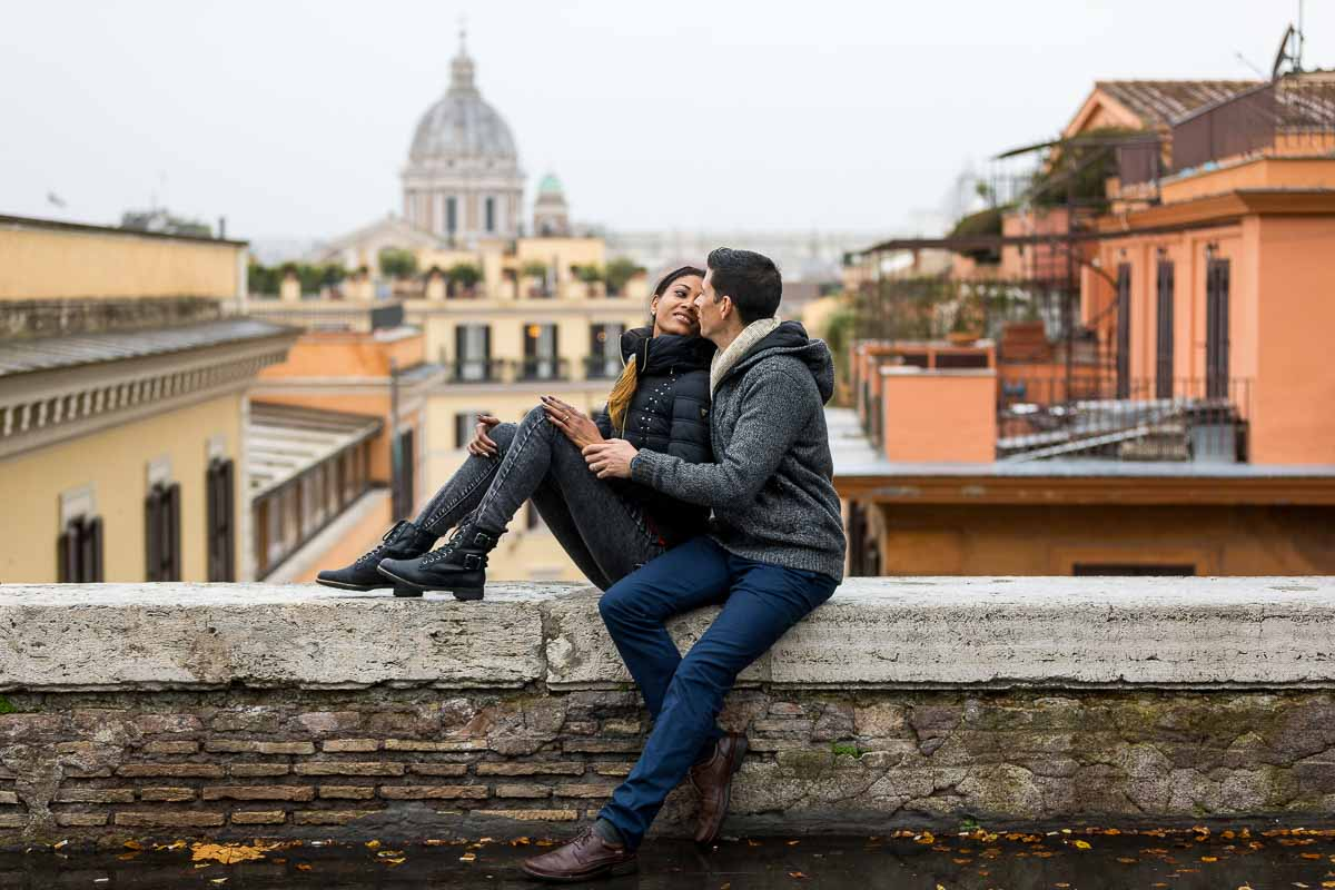 -Couple portrait picture while sitting down before the distant view. Rome, Italy.