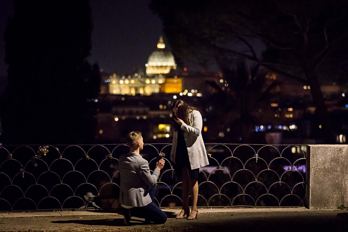 Man kneeling down proposing at night marriage before the sweeping night view of Rome and St Peter's dome in the far distance