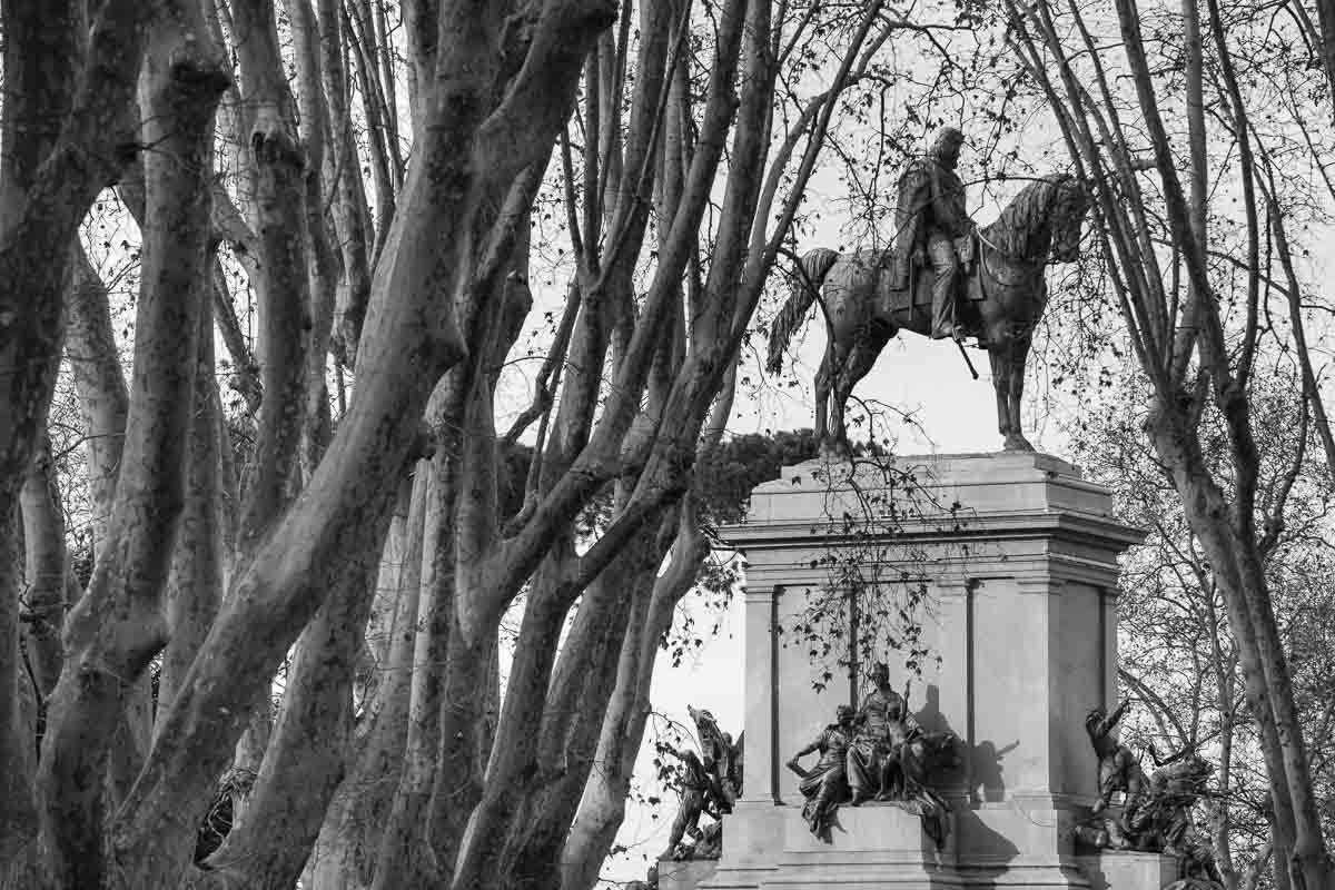The Garibaldi statue seen through trees at Piazzale Garibaldi in Rome. Image in black and white