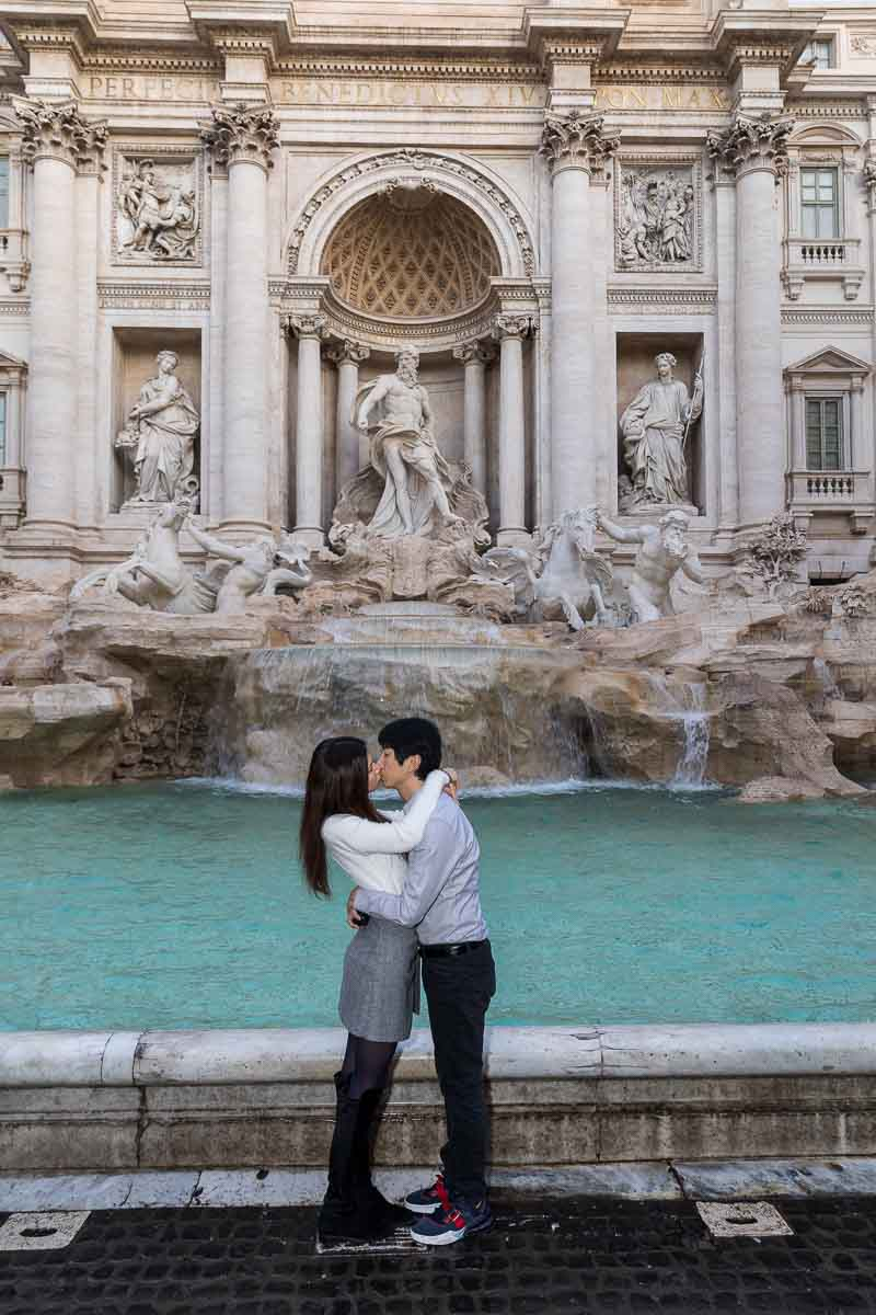 Couple kissing in front of the water fountain with the statues in the background