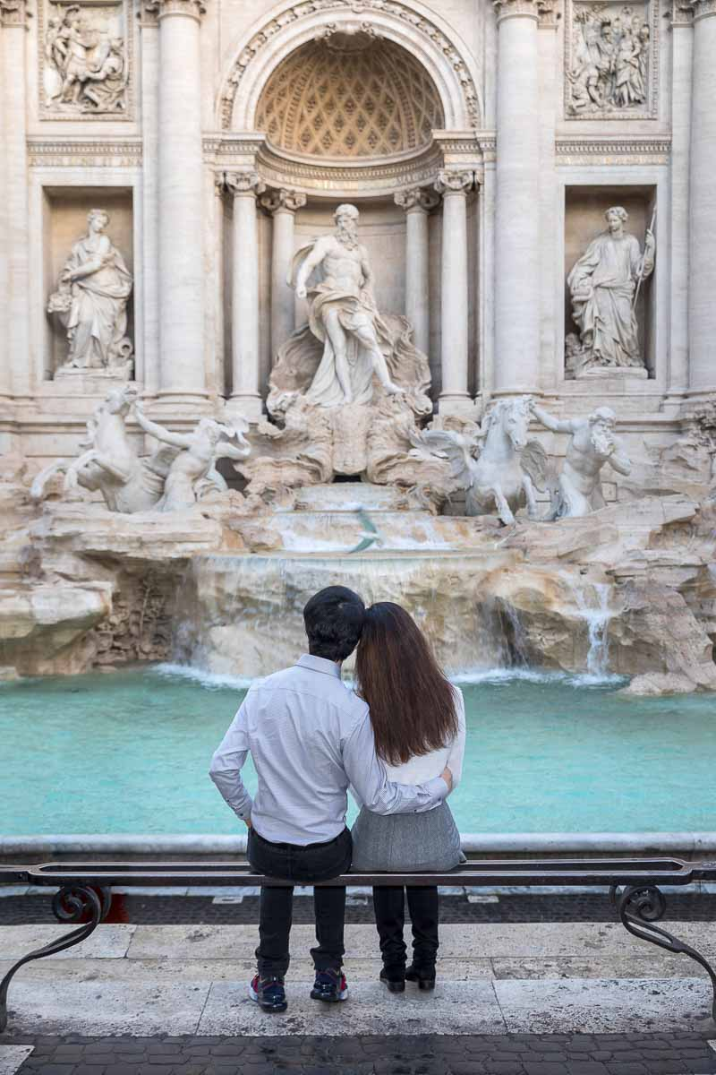 Sitting down romantic photo of being together while admiring Rome's beautiful landmarks like Trevi fountain