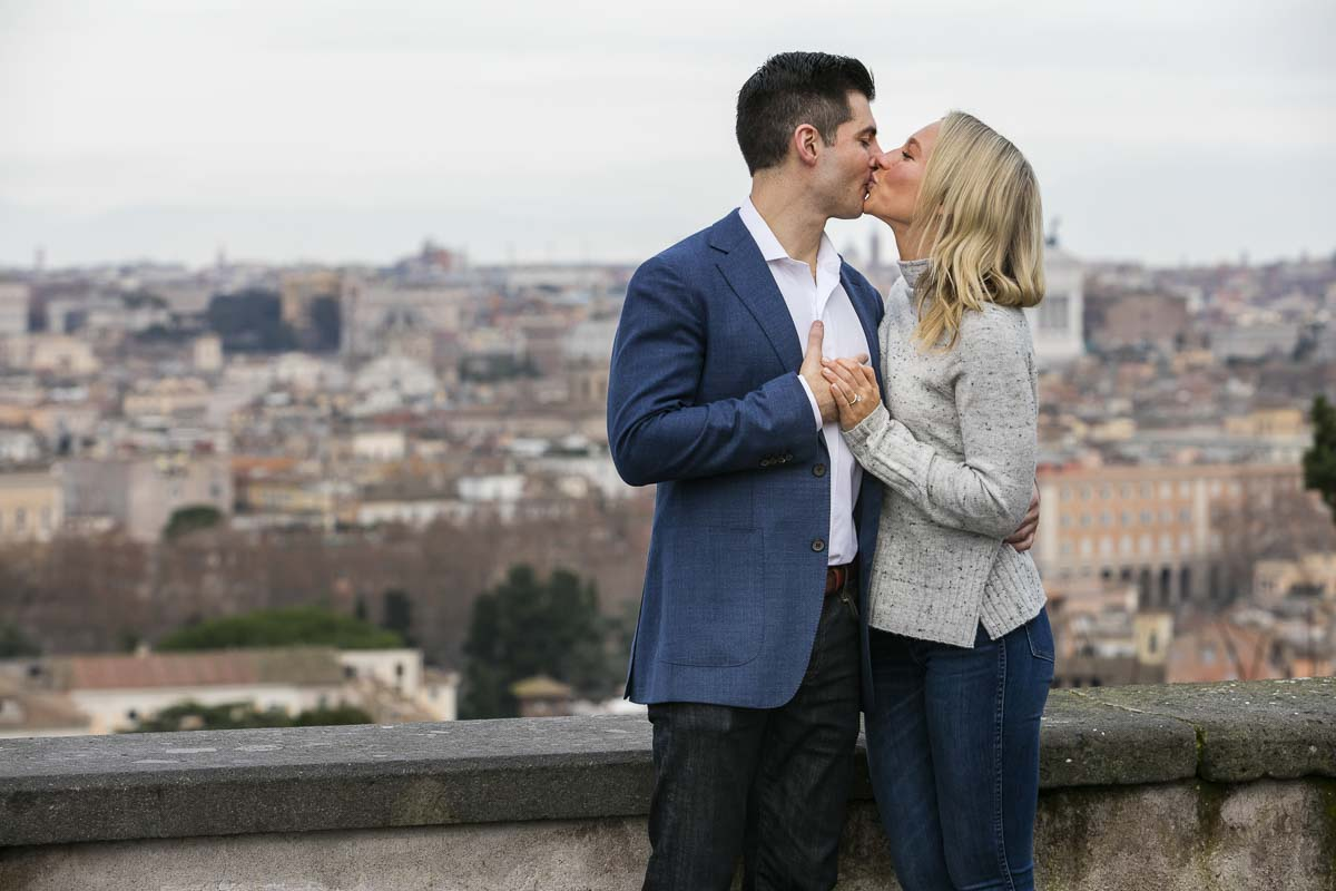 Couple kissing during a photo shoot with the Rome city view in the backdrop