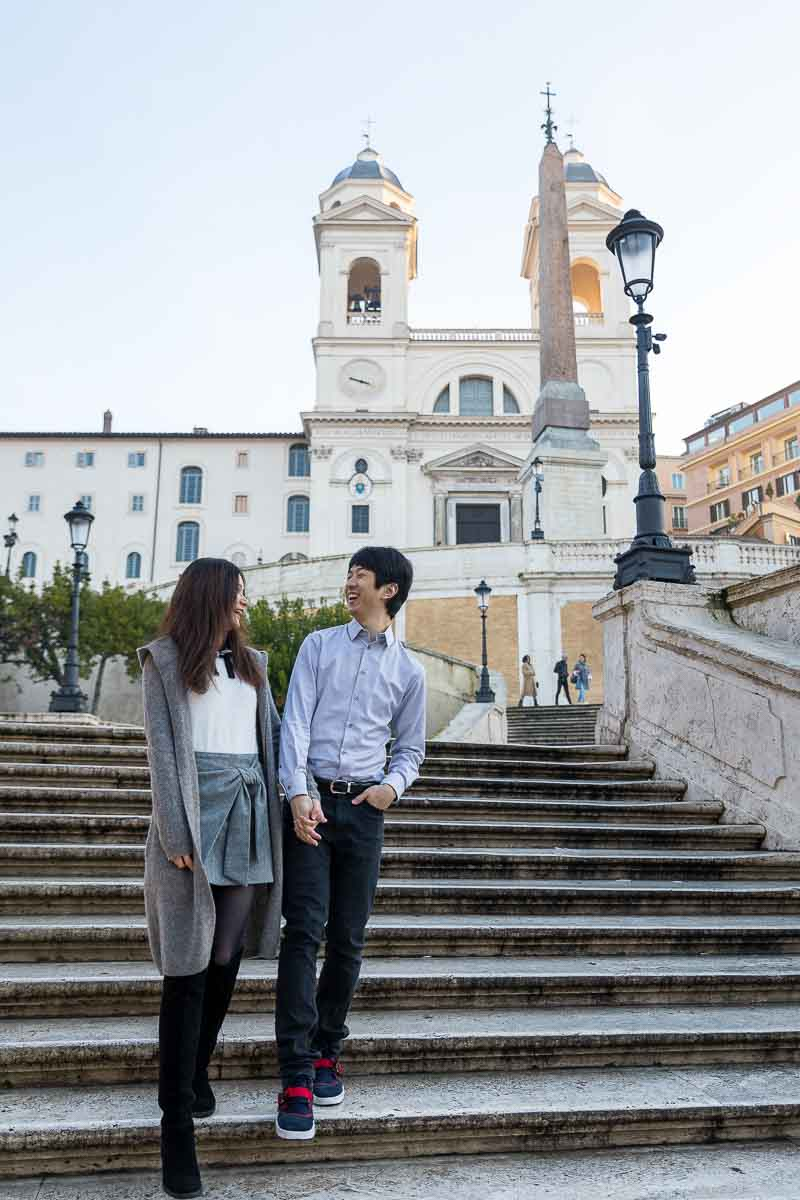 Walking down scalinata di Piazza di Spagna holding hands and enjoying the visit. Engaged Photos in Rome