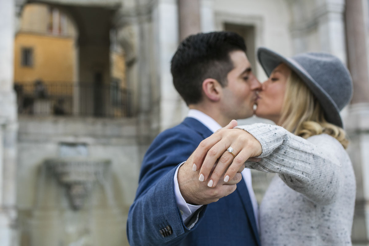 Kissing while showing the engagement ring holding each other hand