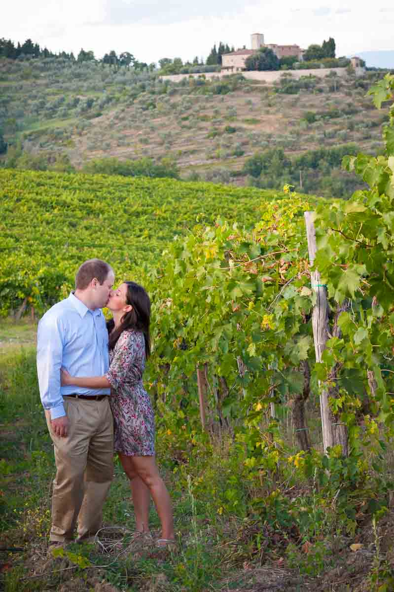 Couple kissing in a vineyard with the tuscany town Greve in Chianti Italy in the far distance