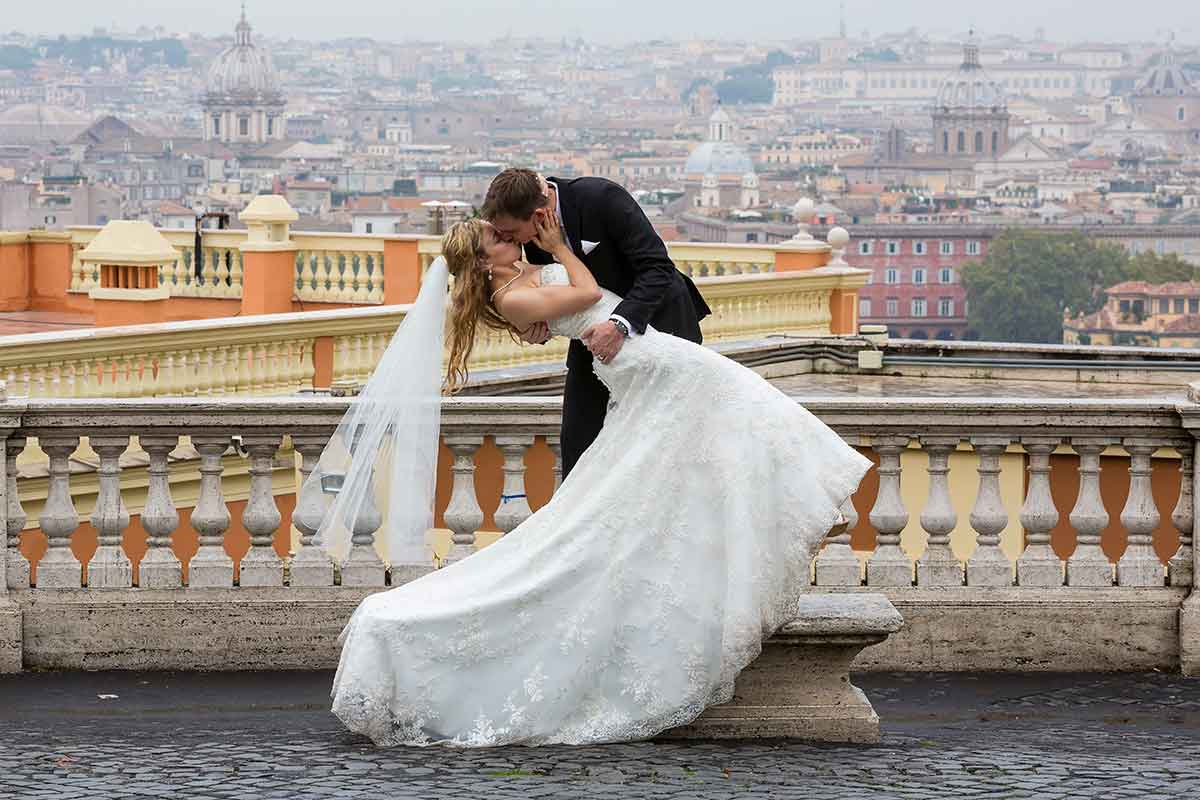 Bride and groom during their wedding day photographed with the city of Rome in the background. Wedding Photographer Italy
