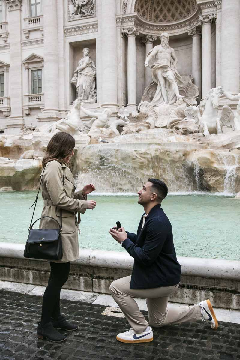 Man kneeling down to ask the most important question! A romantic proposal moment photographer at the Trevi fountain