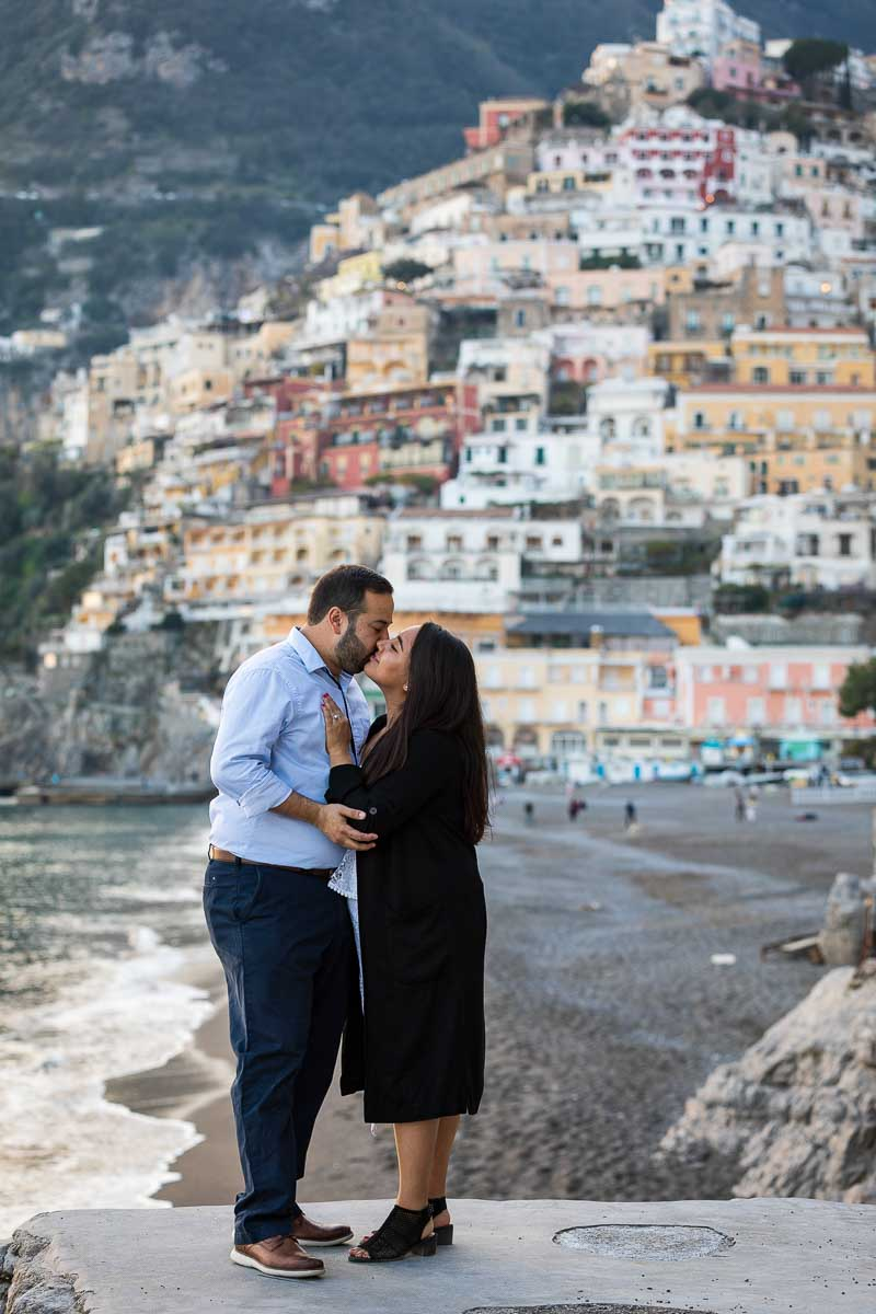 Couple kissing on the beach with the town in the background