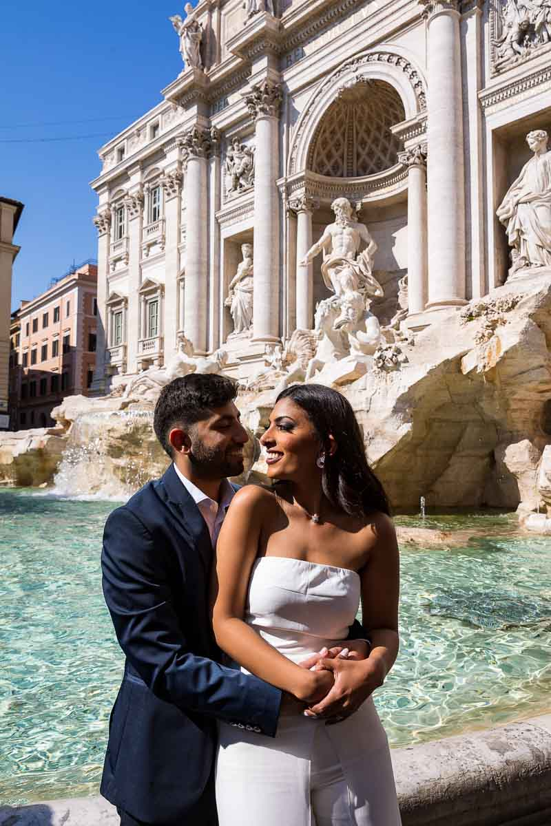 Bride and groom photographed together at the water edge of the magnificent Rome's Trevi fountain