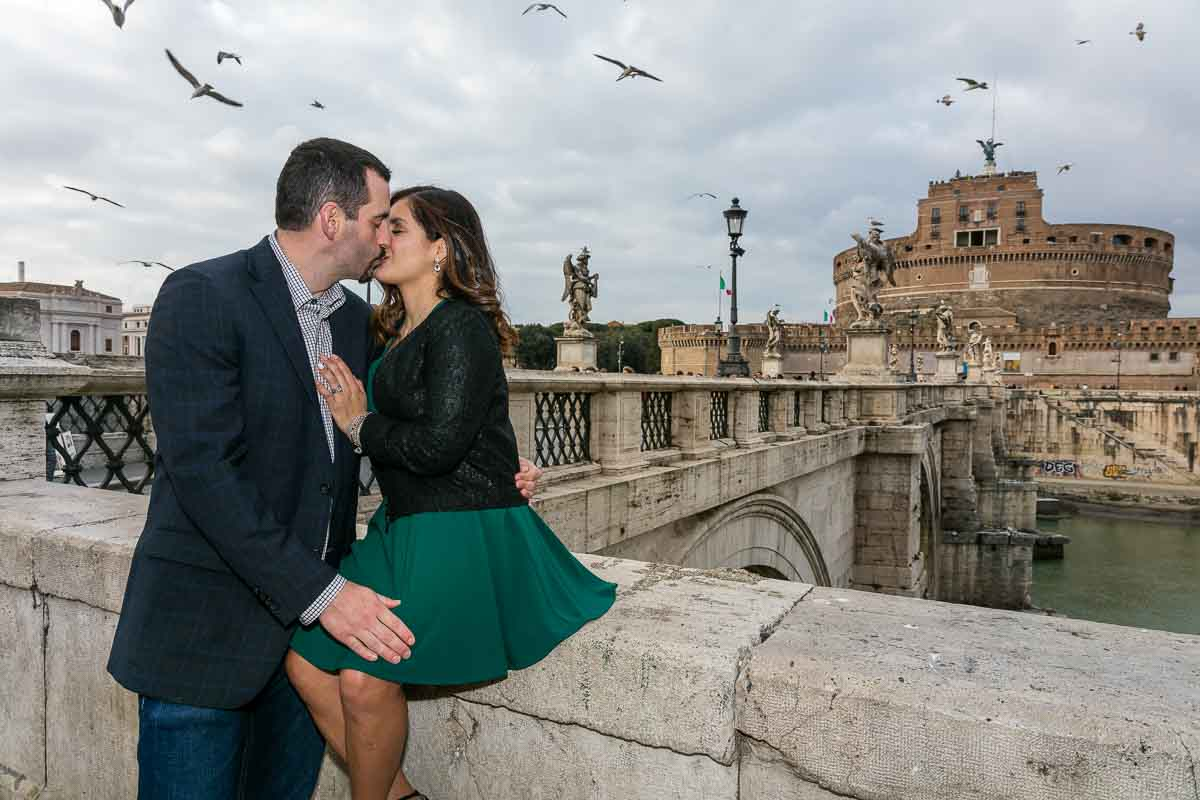 Kissing with Castel Sant'Angelo bridge in the distance and Castel St Angelo as backdrop with birds flying all around