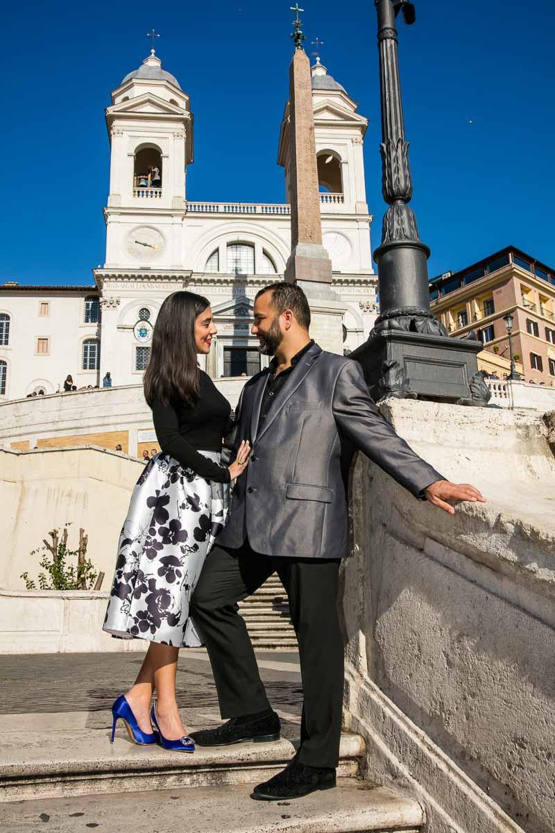 Couple portrait photo underneath church Trinita dei Monti on top of Piazza di Spagna