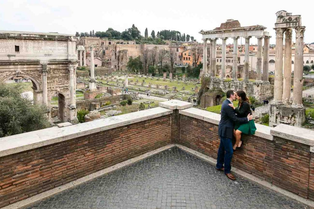 Kissing together before the sweeping view over the ancient roman forum