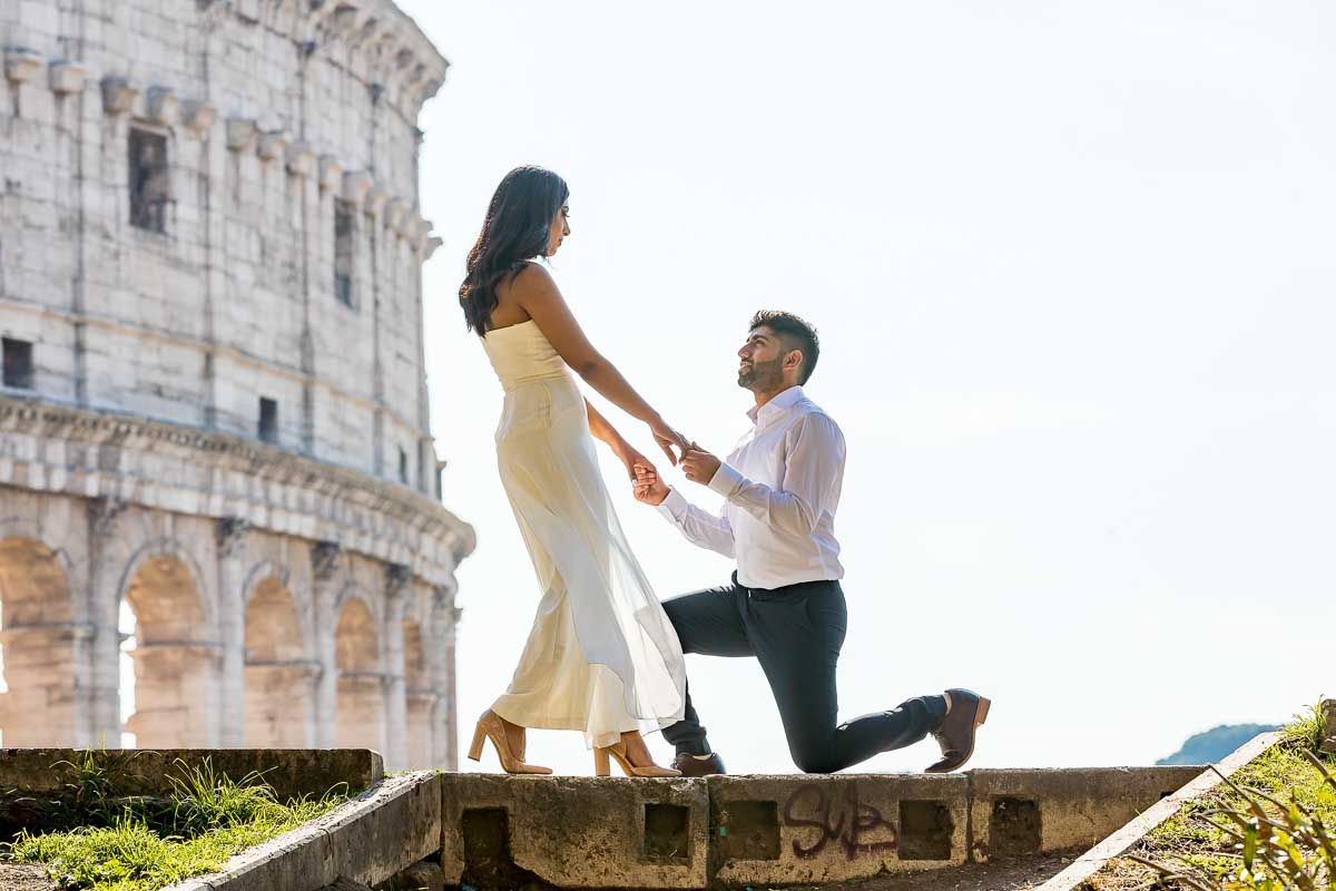 Chivalry moment of groom kneeling down before his wife to be in front of the Coliseum