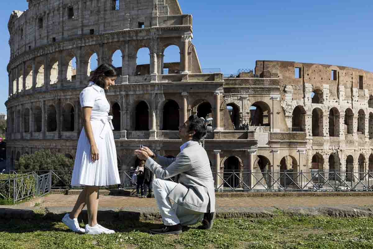 Knee down wedding marriage proposal from the ancient forum with a view over the roman colosseum in the background